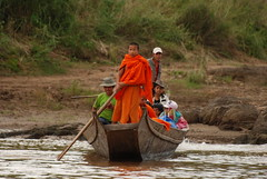 Monk heading up a boat on the Mekong River in Laos
