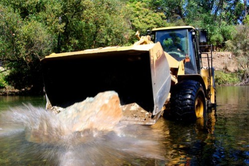 Placing a boulder in the river