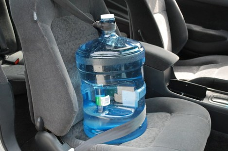 I strap the jug in like a passenger to keep it from moving around. Just make a loop with your seatbelt over the spout!