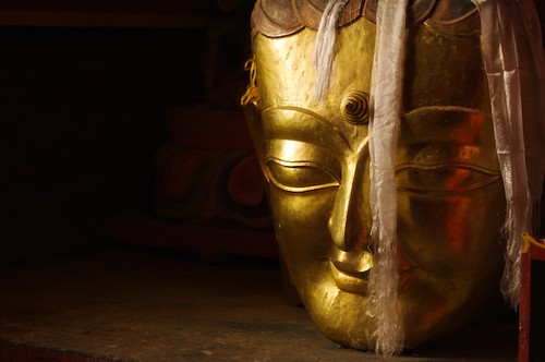 A large carving of Buddhas head sits on a floor in a monastery near XiangCheng, China.