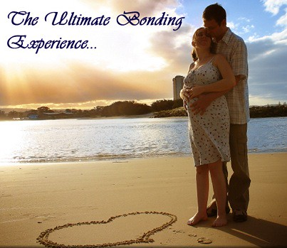 man and pregnant woman hugging on beach, heart drawn in sand