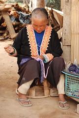 A local Thai woman sews at the first village on our trek