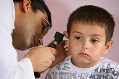 A child receives an ear exam as part of an ove...