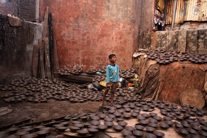Photo of a boy with pottery in Dharavi, by Jonas Bendiksen