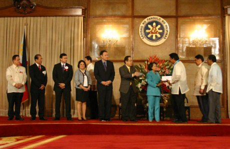 Pres. Gloria Arroyo handing over the throphy to Katangawan Captain Remy Herceda as the other cabinet officers look on.  Behind him are City Councilor Odjok Acharon and DILGs Rudolfo Bernardino.