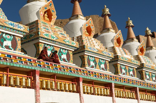 Tibetan Buddhist monks sit on a row of Chortens.