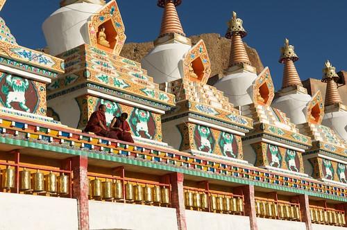 Tibetan Buddhist monks sit on a row of Chortens.