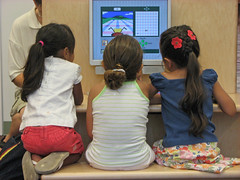 Three girls using the computer at the grand opening.