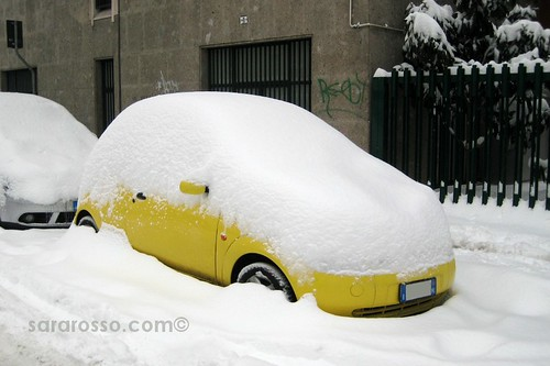 Little yellow car covered in snow, Milan, Italy, December 22, 2009