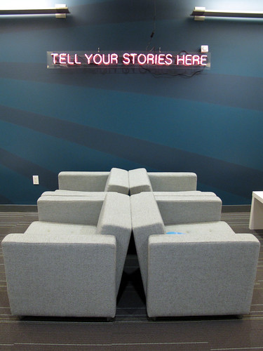 """office with neon sign saying """"tell your stories here"""""""