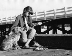 Girl with dog fishing from the dock