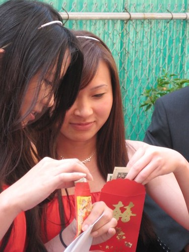 Bridesmaids counting red envelopes