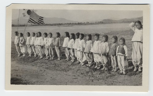 [Line of children (orphans?) with American and Korean flags]