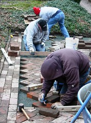 Masons relay brick paving
