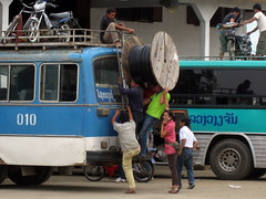 Trying to get a spool of wire onto the top of a bus takes 5 Lao men and one woman on a cell phone