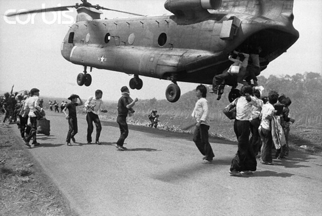 14 Apr 1975, Xuan Loc, South Vietnam --- Refugees hang on for dear life as they attempt to board a giant Chinook helicopter as it was taking off here following a supply drop to troops fighting along Highway One, some 38 miles northeast of Saigon. --- Image by © Bettmann/CORBISs