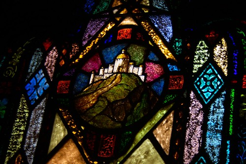 Stained glass window depicting a city on a hill
