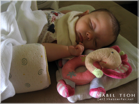 Snoozing away next to her rattle toy