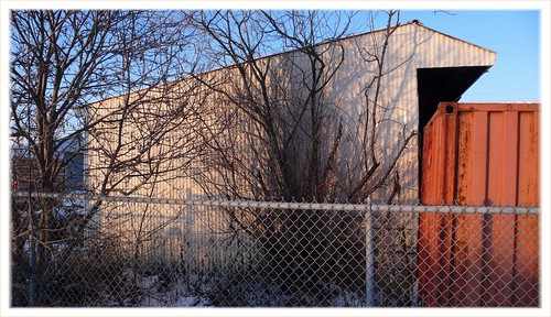 tan shed and red shipping container