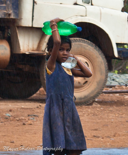 A Small Girl Carries Water Bottles While It Starts Raining by donteatthis