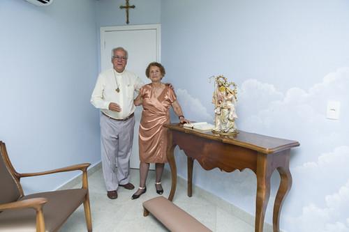 Na capela da nova sede, Padre Geraldo Ildeu e Dona Lilá Salles, antiga proprietária do imóvel