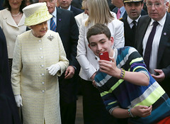 BELFAST, NORTHERN IRELAND - JUNE 24:  A local youth takes a selfie photograph in front of Queen Elizabeth II during a visit to St George's indoor market on June 24, 2014 in Belfast, Northern Ireland. The Royal party are visiting Northern Ireland for three