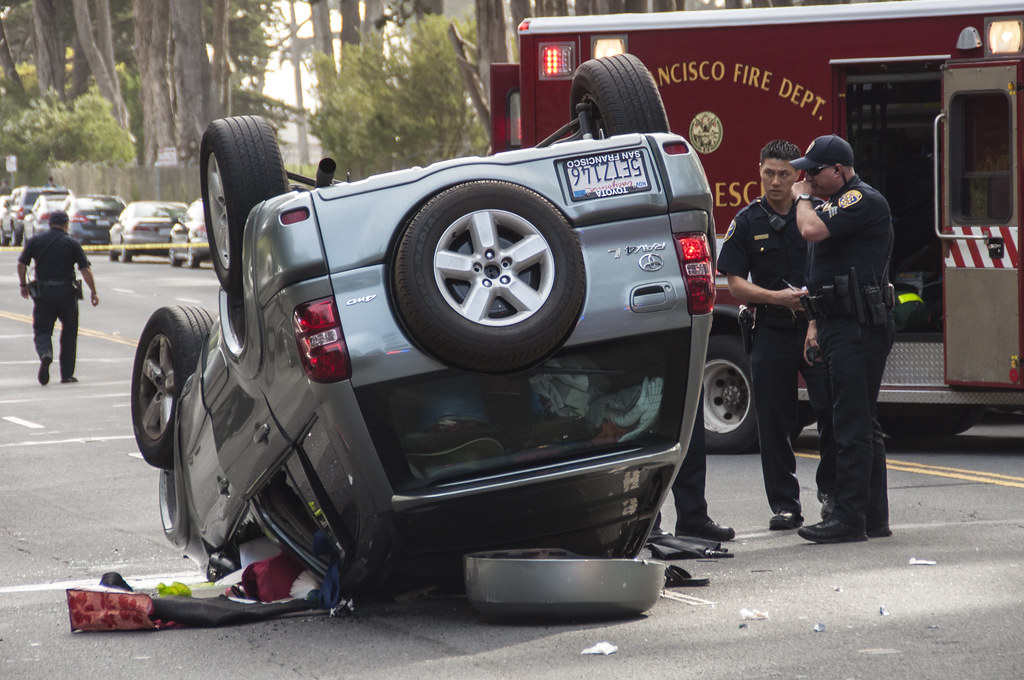 SFPD officers investigate the scene after a driver blacked out and flipped their car on Lake Merced Boulevard between Font Boulevard and Higuera Street around 2:30 p.m. Thursday, March 6. Photo by Jessica Christian / Xpress