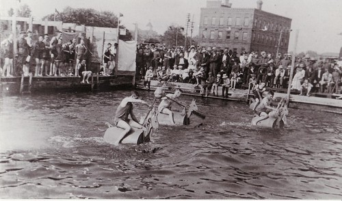 Men racing on barrels shaped like horses in the water by the wharf in Deseronto