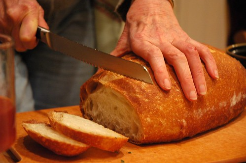 Cutting warm bread, at Q's party, Broadview Neighborhood, Seattle, Washington, USA