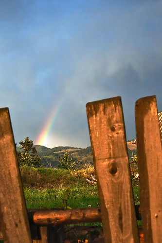 Long visible rainbow in the sky through wooden fence