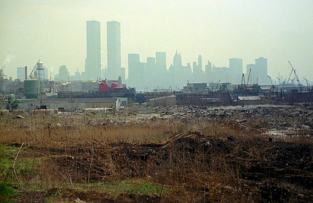 Jersey City. Industrial wasteland with the World Trade Center and Lower Manhattan in the distance. The old chromium plant on Henderson Street at left middle. 1975