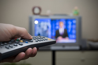 Image of a television remote pointed at an out of focus tv set.