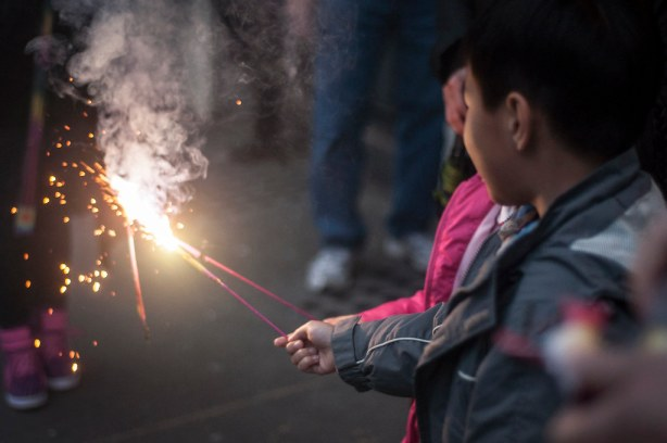 Children light sparklers and other fireworks on Clay Street during San Francisco's Chinese New Year Parade Saturday, Feb. 15. Photo by Jessica Christian / Xpress