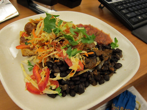 white plate with black beans, salsa, shredded veggies, and potentially a taco shell.