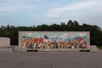 Inmiddels waren we aangekomen bij de Arc de Triumph van Pyongyang waar je ook deze muurschildering van de grote leider, die een geweldige toespraak geeft, kunt zien.