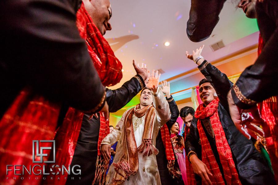 Groom and groomsmen dancing during Indian Ismaili wedding