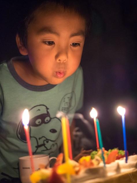 6才誕生ケーキのろうそくを消す