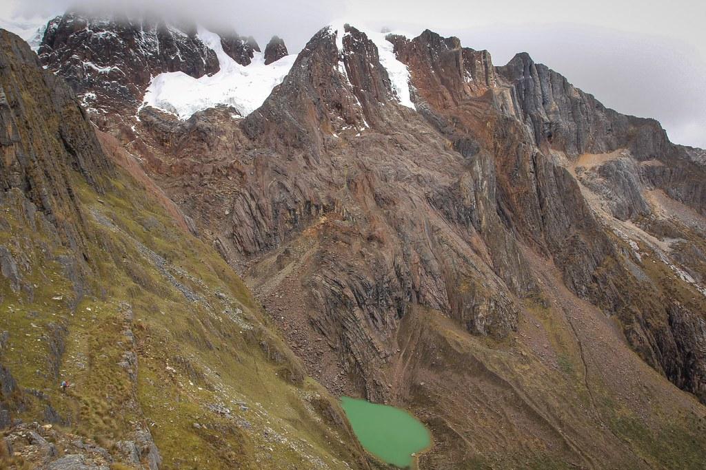 Coming down from Alto de Pucaraju pass (4650m) with the east face of Taulliraju (5830m) touching cloud. Can you spot Katrijn? Huascaran National Park. Cordillera Blanca. Peru.