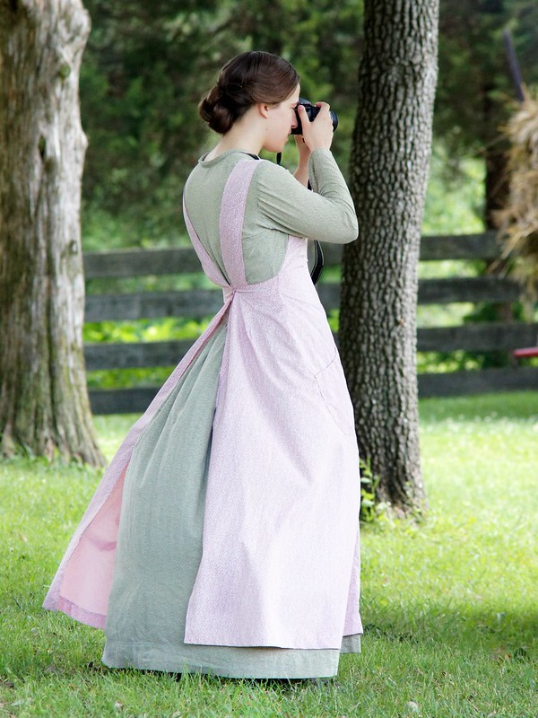 Young woman's in period dress is looking through the viewfinder of a modern camera.