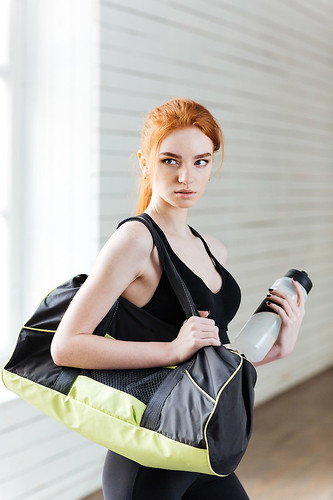 Young woman with bottle of water and sports bag