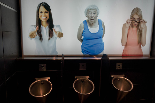 Photos of Women Above Urinals Reacting To Men Using the