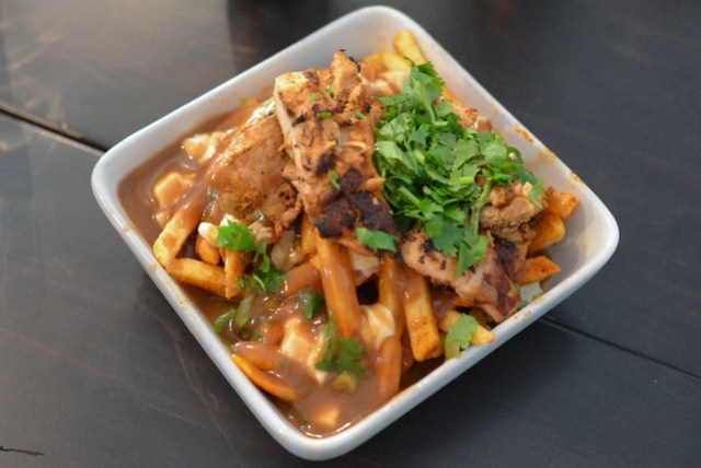 Chicken Tikka Poutine crisp masala fries topped with chicken tikka and cheese curds, doused in brown gravy