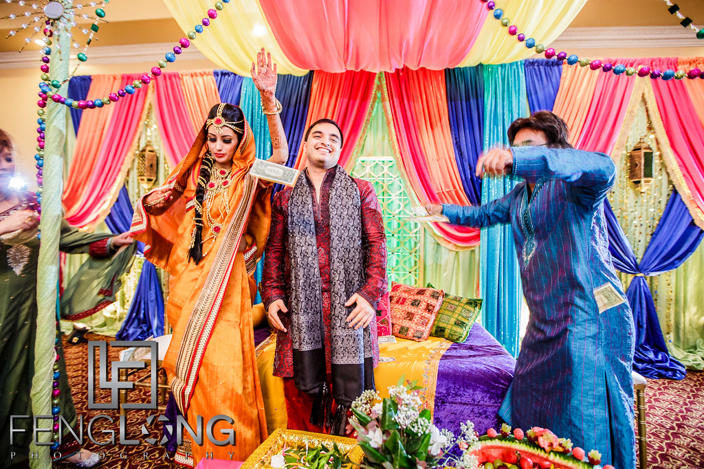 Bride and groom dance on stage during entrance on Mehndi night while guests throw money on them