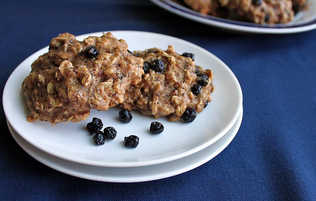 Stacked white plates with two big, puffy, blueberry-studded oatmeal cookies.
