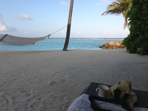 Private beach view with hammock and chaise loungers.