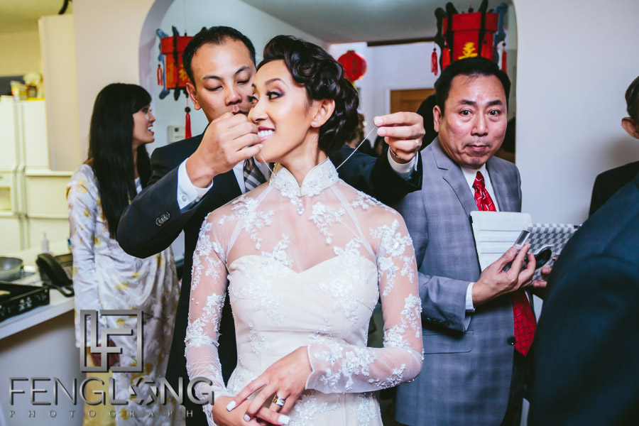 Vietnamese groom puts necklace on bride during wedding