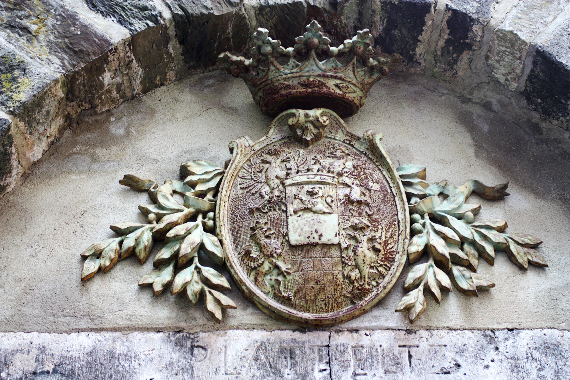 A stone crest above the entrance to the courtyard of the castle.