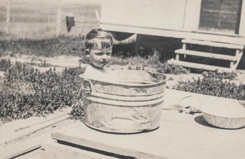 Grumpy little boy sitting in a bucket
