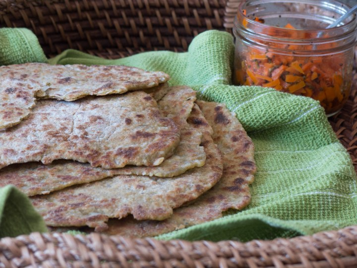 zucchinie and thyme flatbreads in a basket with a green napkin, served with carrot relish