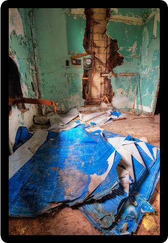 A pile of old blueprints in a run-down room